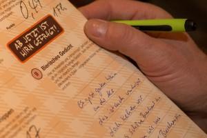 Flyer mit Gedicht, Hand mit Kugelschreiber